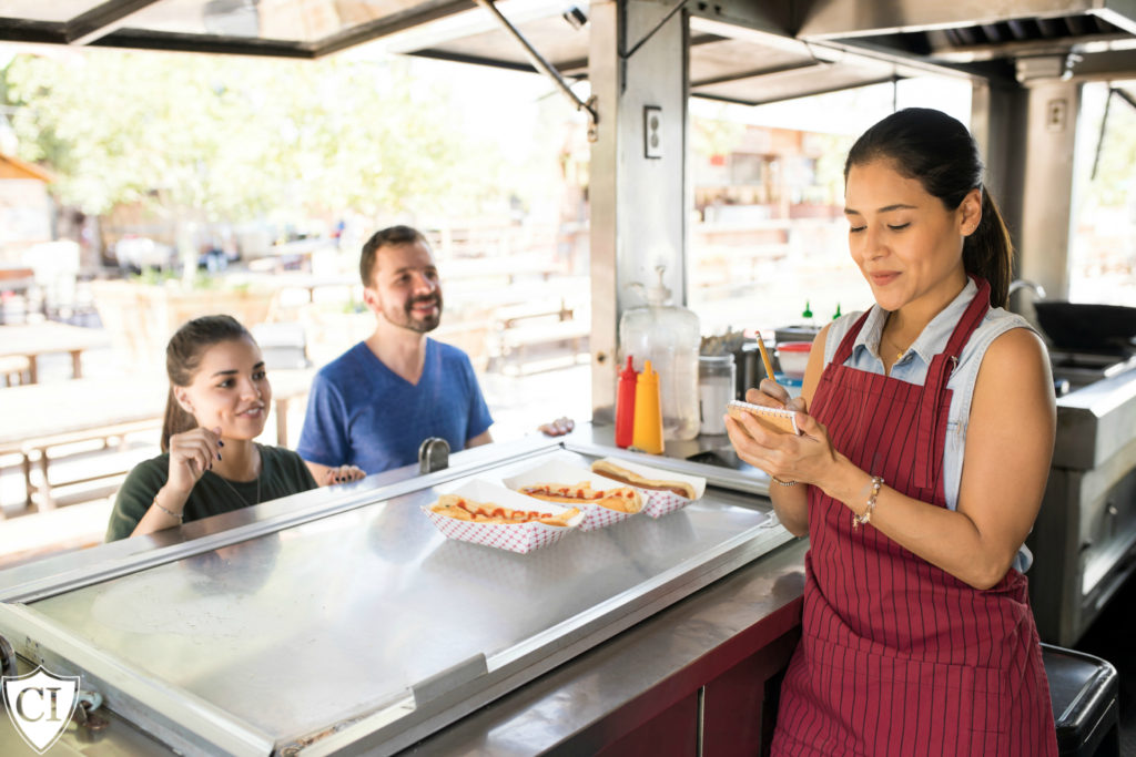 Food truck owner taking orders from her customers.