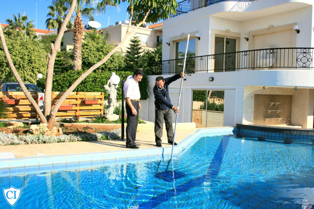 Swimming pool cleaner skimming pool with property owner standing beside them.
