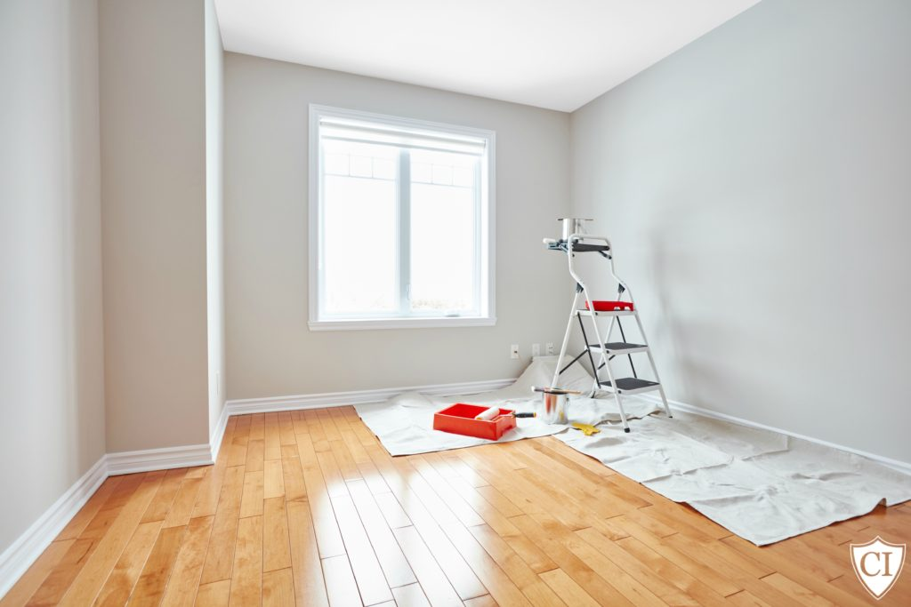 Step ladder and painting tools in modern room. Apartment renovation background.
