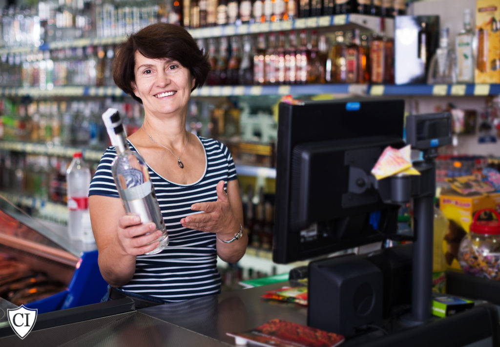 cashier holding liquor bottle toward camera standing by cash register