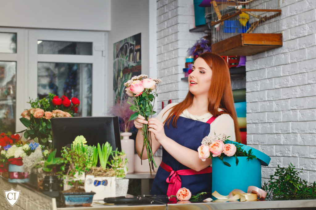 Person with long red hair wearing a smock, putting together a floral arrangement in a florist shop.