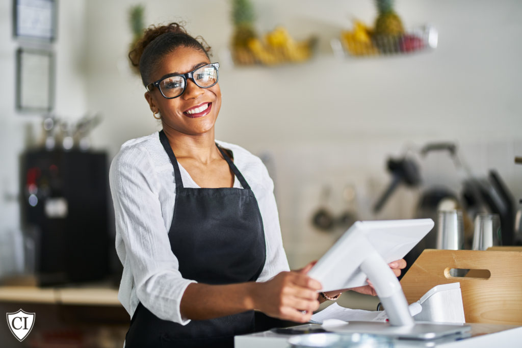 Woman standing at cash register in retail store smiling at camera